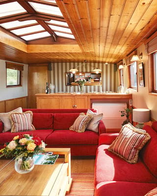 Lounge of a luxurious river barge with red-cushioned sofas and a pine-clad ceiling