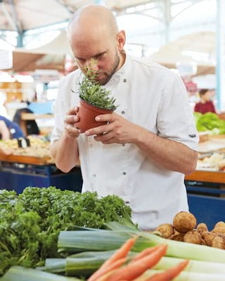 Chef in chef whites smelling fresh herbs in a little pot from a food market