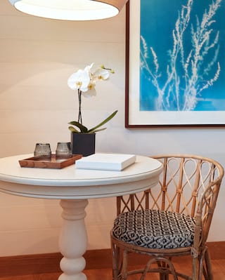 Blue wave print above a wicker chair beside a coffee table topped with an orchid