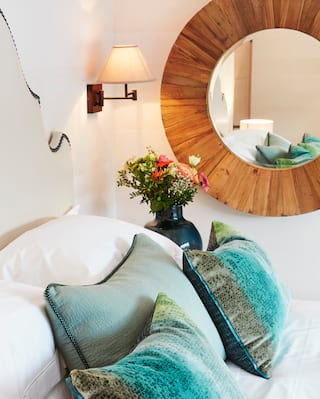 Vibrant cushions on a plush bed next to a circular mirror with an oak frame