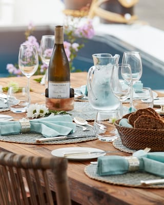 Close-up of a polished oak table, topped with tiffany-blue napkins in silver rings