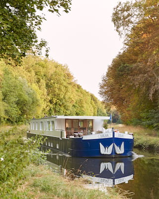 Front view of a luxurious river barge sailing down a sun-splashed tree-lined canal
