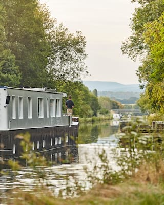 Navy bottomed luxury barge drifting down a rural tree-lined river in a lush valley