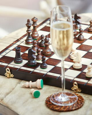 Glass of with champagne beside a wooden chess board with carved chess pieces