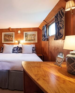 Lamplit wood-panelled barge cabin with a pillowy king-bed with navy blue accents