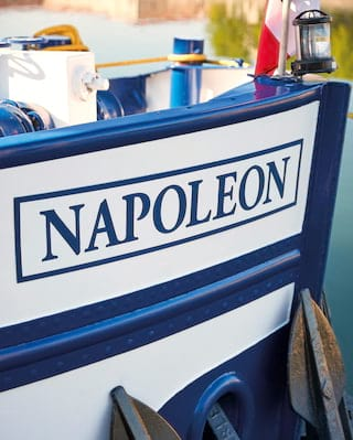 The pristine white side of a luxury barge with 'Napoleon' painted in blue lettering