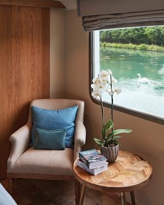 Orchid and books on a side table next to a plush warm grey armchair