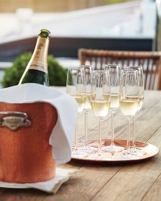 Bottle of Laurent Perrier champagne in a cooler beside filled flute glasses