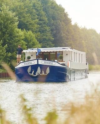 Blue bottomed luxurious river barge sailing along a tree-lined river