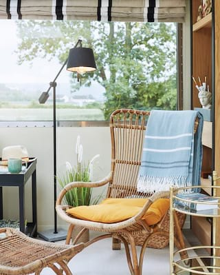 Stylish wicker chair with a baby blue cashmere blanket and yellow cushion
