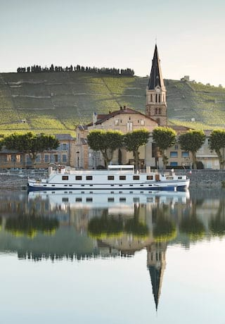 Luxury river barge sailing past a small village in Alsace, France