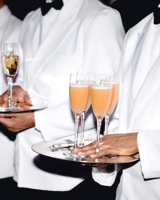 Hand holding four peach Bellini cocktails in flutes on a silver tray