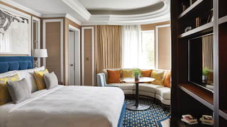 Hotel suite with circular sofa area and large bed, with muted blue and tan accents
