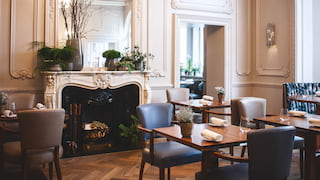 Light and airy restaurant with contemporary furniture and large regency fireplace
