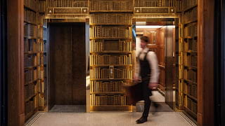 Lift lobby surrounded by book lined cases with mosaic tile floor