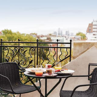 Suite terrace overlooking London with a circular table laden with breakfast