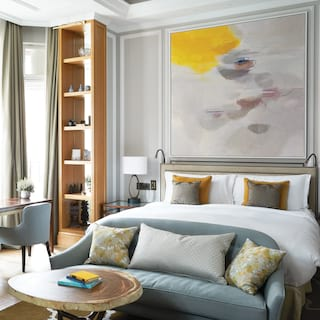Plush seating area before a large pillowy bed with contemporary artwork above