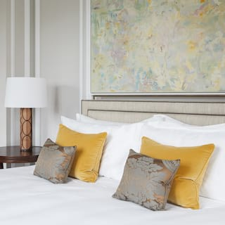 Large pillowy bed with mustard yellow cushions and pastel-coloured artwork above