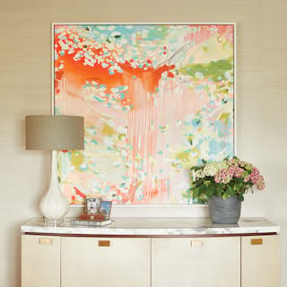 Hotel room side cabinet with marble top, flower bouquet and pastel artwork above