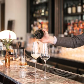 Barman pouring champagne into two champagne flutes on a marble bar