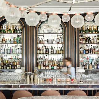 Elegant bar with three arches containing shelves of liquor bottles