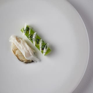 Birds-eye-view of circular white plate with contemporary British cuisine