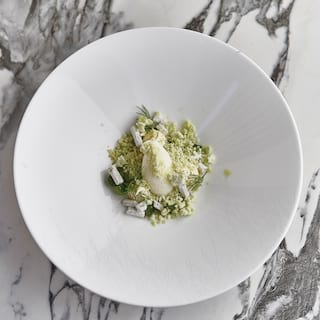 Birds-eye-view of a white circular bowl with a contemporary pistachio dessert