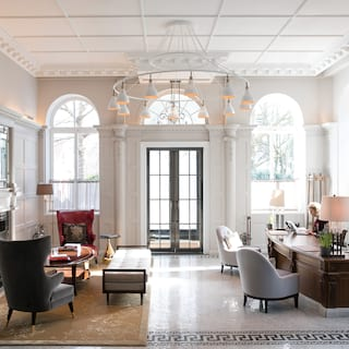 Elegant regency-style double-height guest lobby with contemporary wooden desk