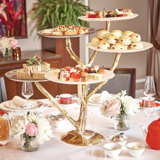 Gold tiered afternoon tea stand laden with sweet delicacies