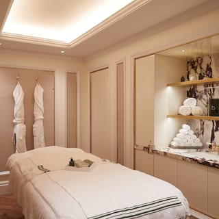Spa treatment room with dusky pink panelled walls and hanging bathrobes