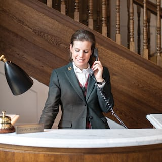 Smiling concierge on the telephone at a marble-topped desk