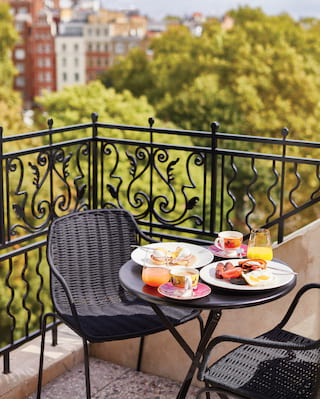 Close-up of a hotel suite terrace seating area and table laden with breakfast