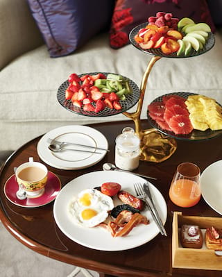 Wooden table laden with breakfast food and a tiered platter with fresh fruit
