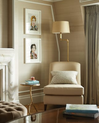 Hotel room lounge area in muted cream tones with large open fireplace