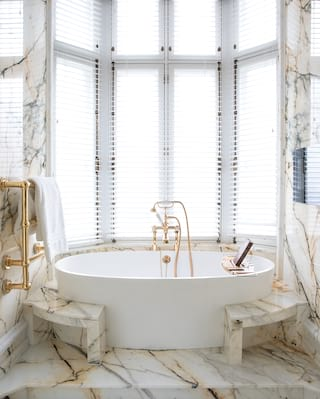 Marble bathroom with a large oval standalone bathtub tucked into a bay window