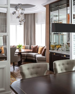 Hotel suite dining area with a polished wood table and contemporary grey chairs