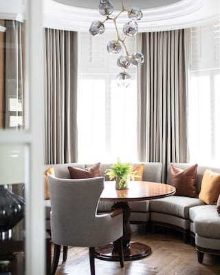 Suite lounge with a circular table and banquette seating in grey and tan hues
