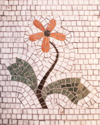 Close-up of a mosaic orange flower among pearly white tiles