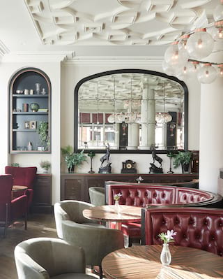 Light and airy bar room with circular banquette seating in plum and grey hues