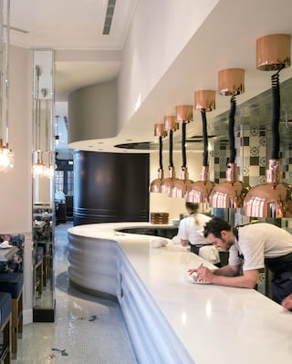 Long marble-top kitchen counter lined with copper bowl lights and chefs baking