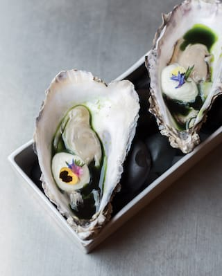 Two large oysters garnished with edible flowers on a rectangular platter