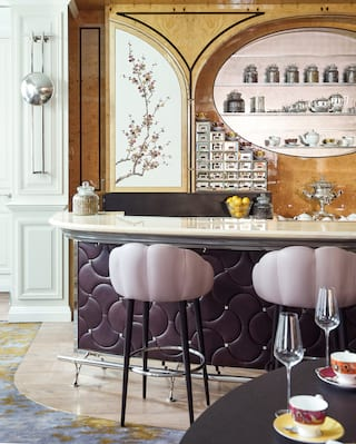Two dusky pink stools under a marble bar top with tea pots in an oval shelf above