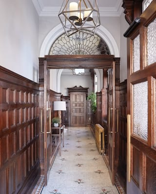 Double-height corridor with gleaming dark wood panelled walls and mosaic floor