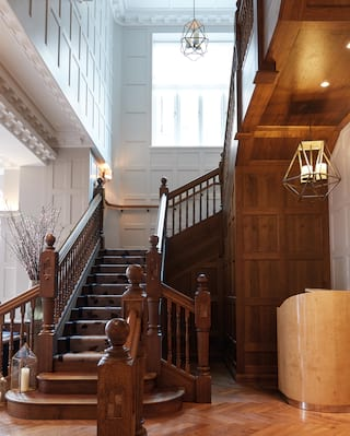 Grand polished wooden stairway with wood-panelled walls and gleaming balustrade