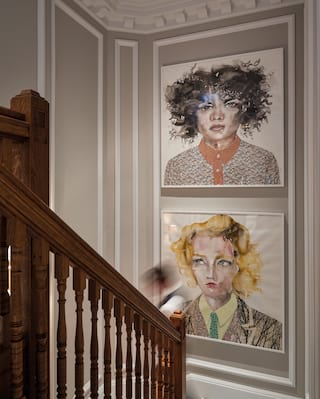 Close-up of two contemporary portraits hung one above the other