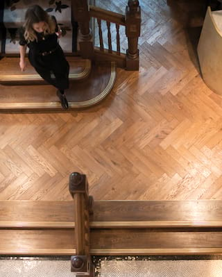 Birds-eye-view of a lady walking down a staircase onto a parquet floor