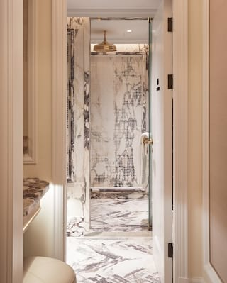 Spa shower with marble tiles and brass rain shower head