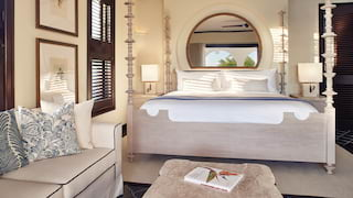Bright and airy hotel room with a pillowy bed and circular mirror above