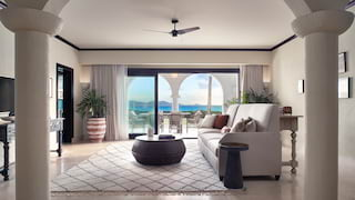 Hotel suite lounge with light furnishings and Caribbean Sea views