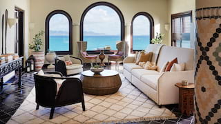 Hotel suite lounge with light and dark furnishings and arched windows